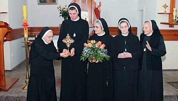 zdjęcie grupy sióstr w kościele z hostią